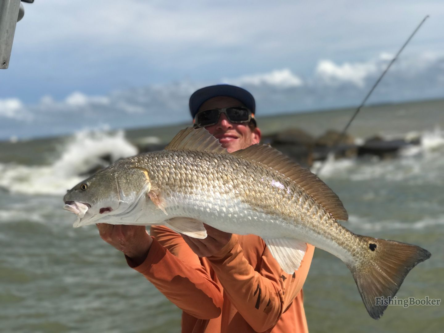 Angler holding a big Redfish he caught in Galveston.