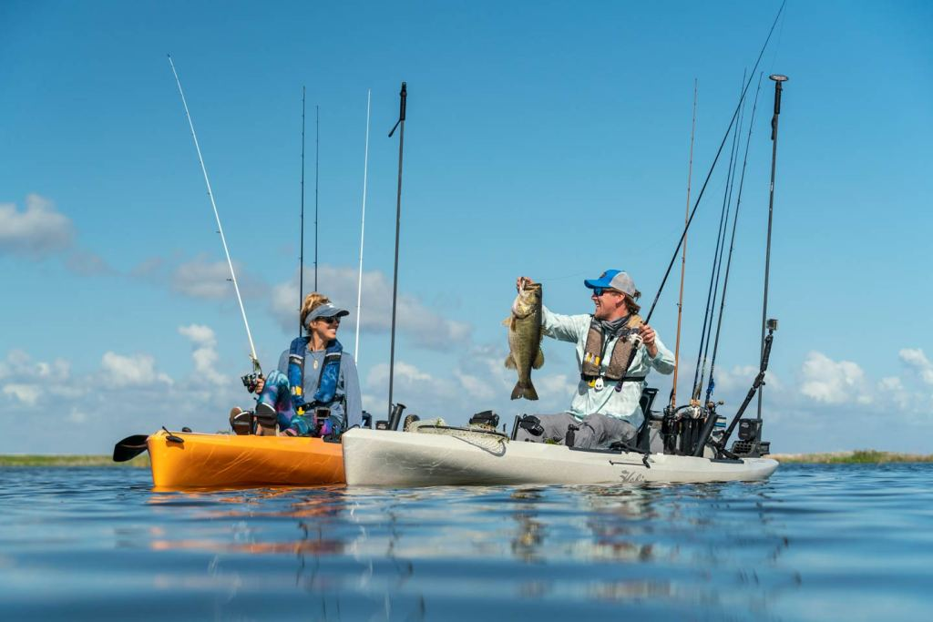 Two kayak anglers on a lake in Croatia smiling having caught a Bass
