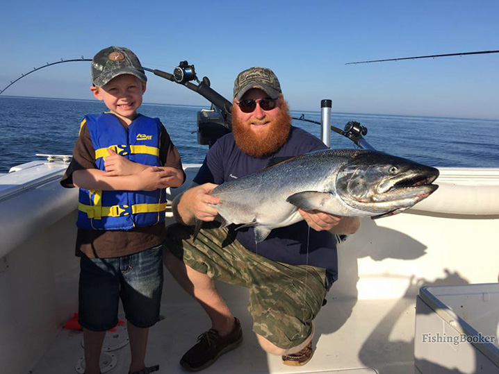 A dad and his son fishing on Lake Michigan and holding big fish.
