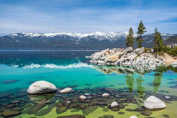 Lake Tahoe waters with mountains and pine trees in the background