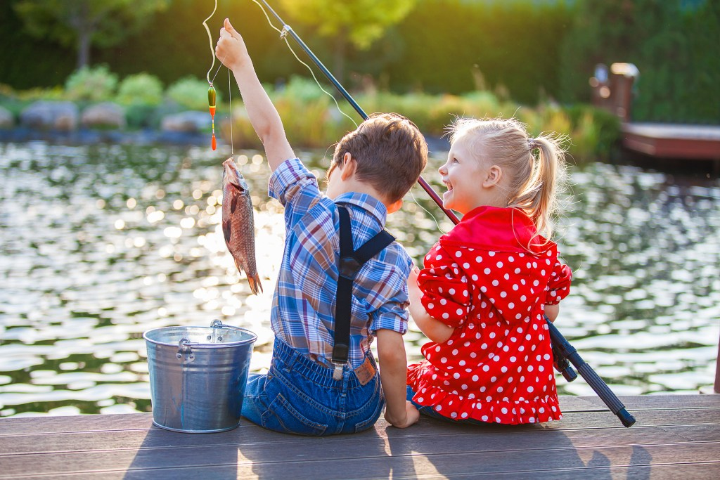 little boy holding a fishing line with a fish on it, and a little smiling girl sitting next to him, holding a rod