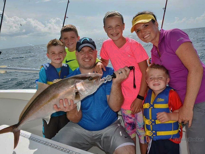 Parents and four kids on a family fishing charter in Myrtle Beach, holding a Redfish.