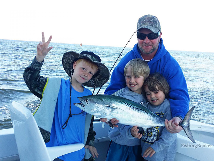 A dead and three kids on a family fishing trip in Nags Head holding a Bonito