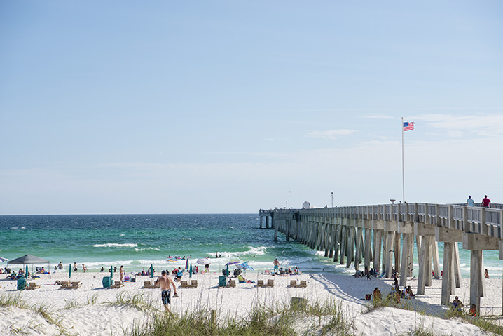 Panama City Beach fishing pier with many people sitting on a sandy beach that looks onto the ocean