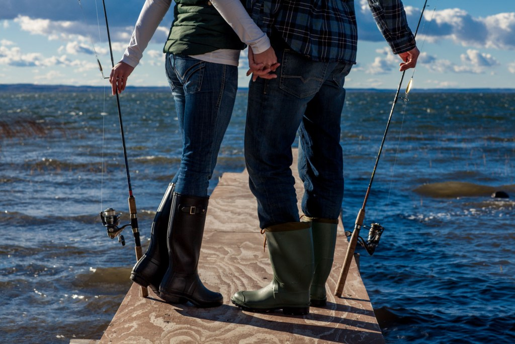 A girlfriend and boyfriend standing together by the water holding fishing rods.
