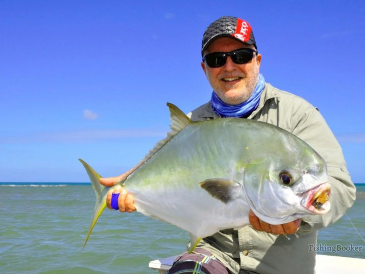 A smiling angler holding a Permit