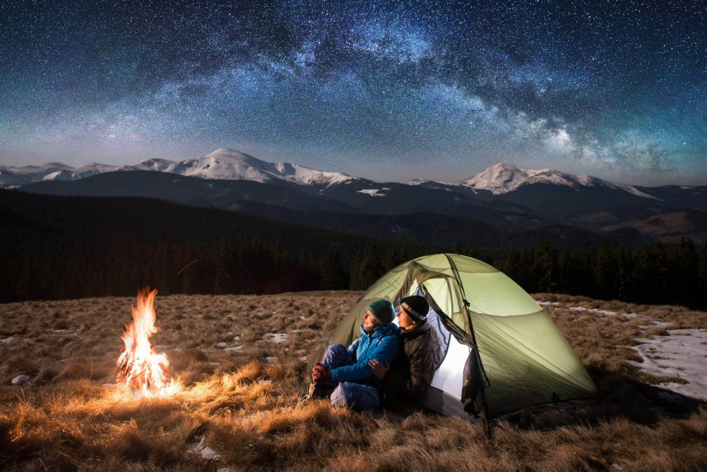 A couple in a tent on a Valentine's Day date next to a bonfire with mountains and stars in the background.
