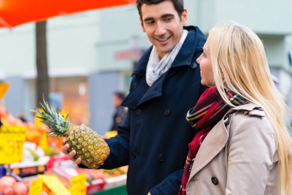 A couple in a Farmers Market buying a pineapple.