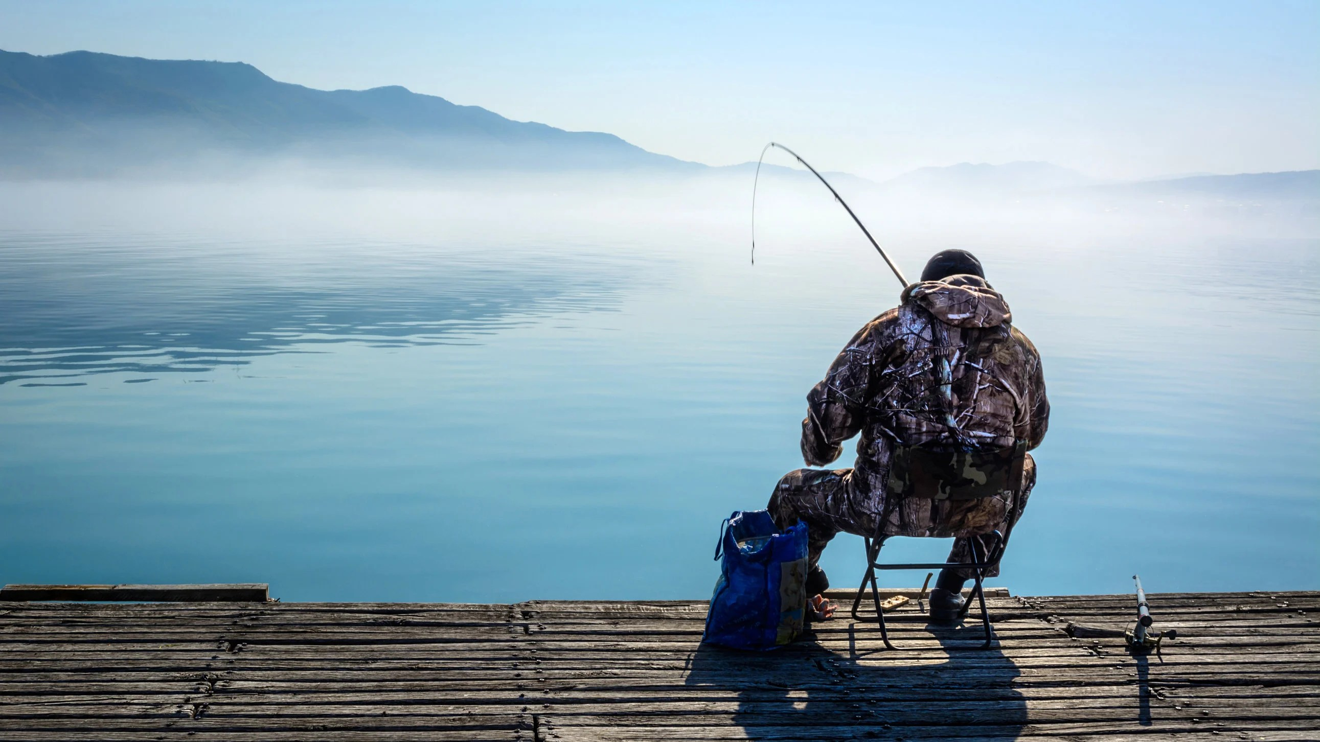 a sitting pier angler with a fish on