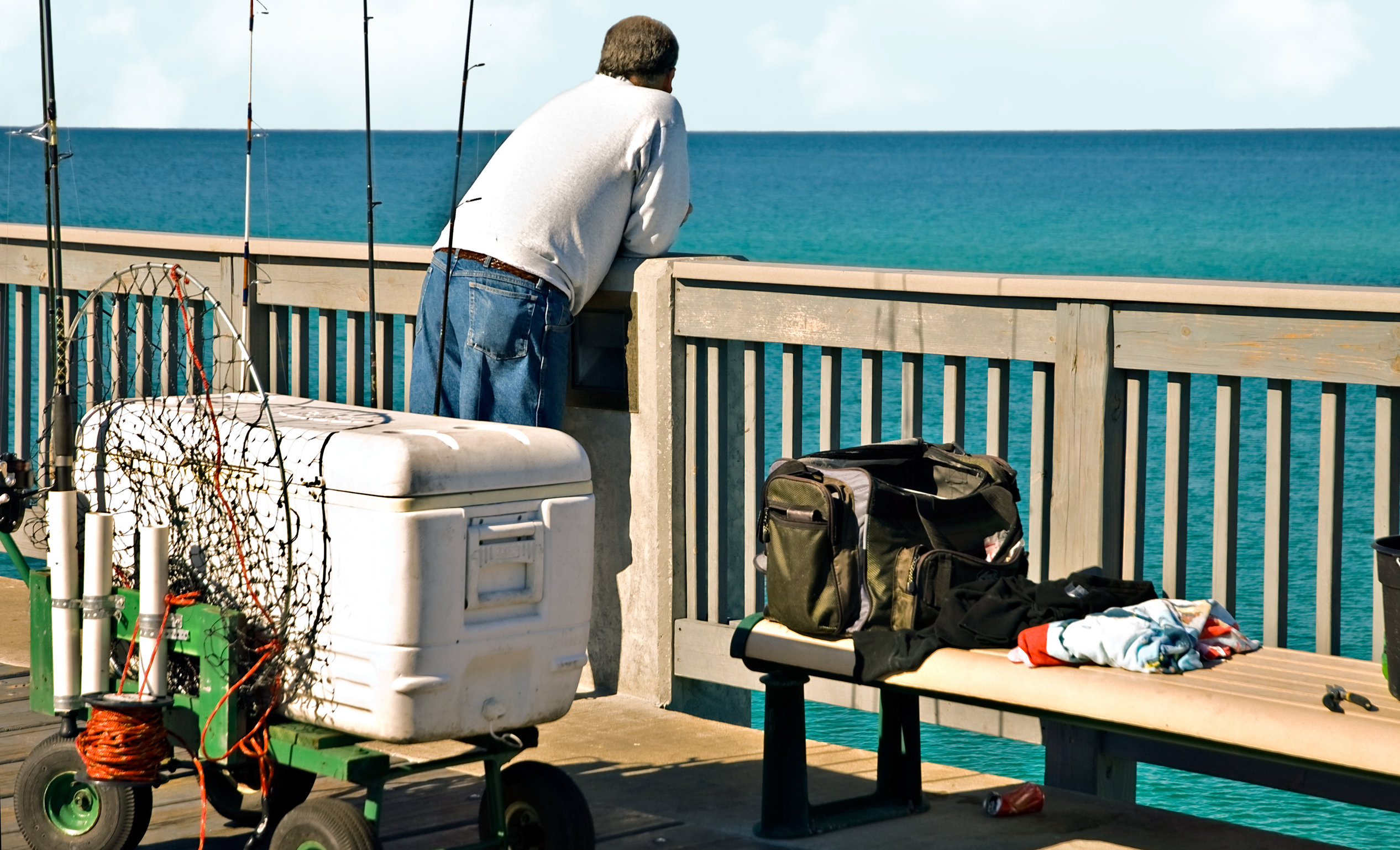 pier fishing gear with an angler leaning on the railing of the pier and the sea in the background