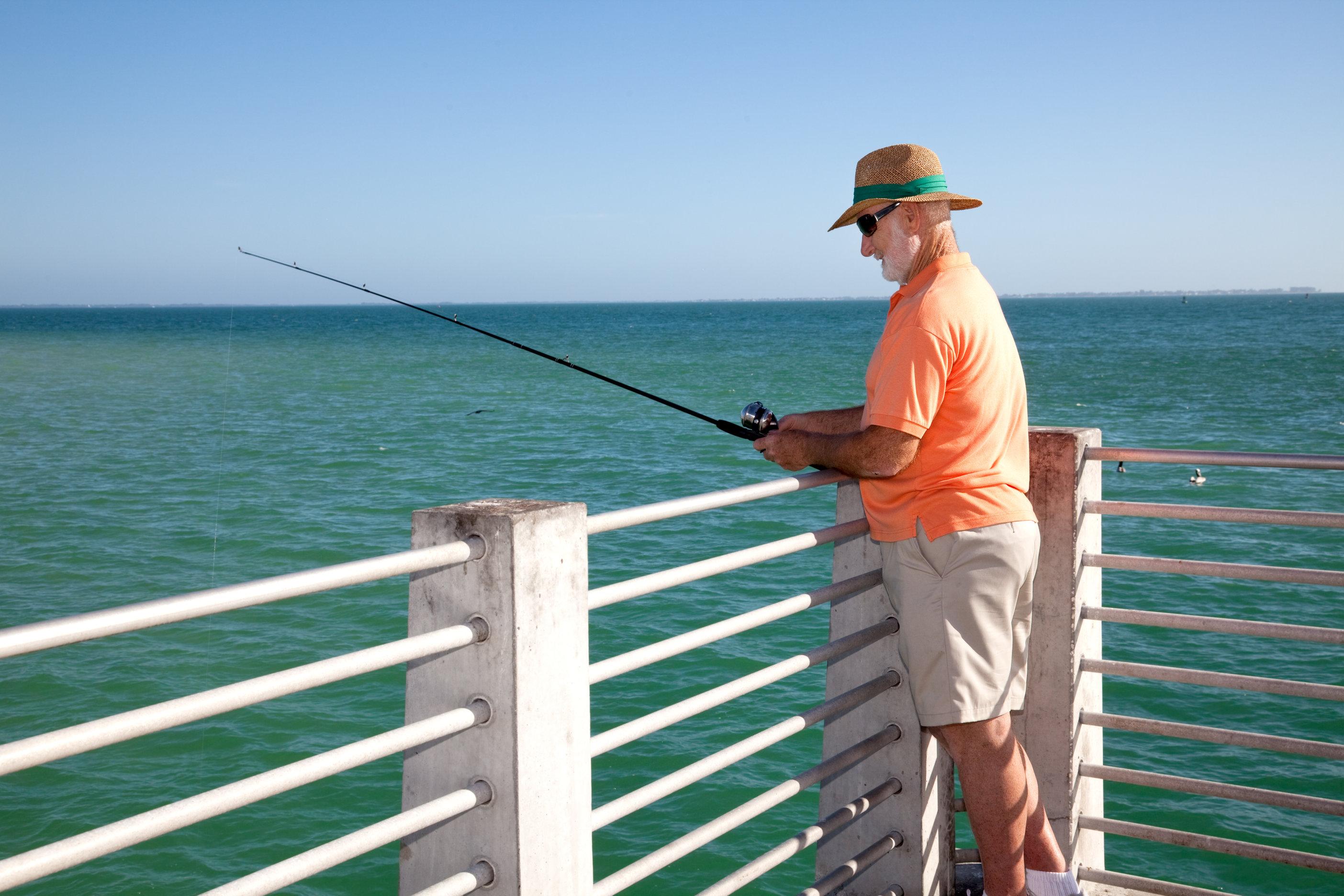 senior angler fishing from a pier