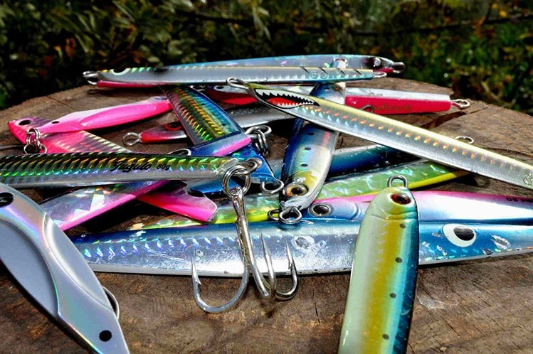 A selection of colorful shore jigging lures on a tree stump