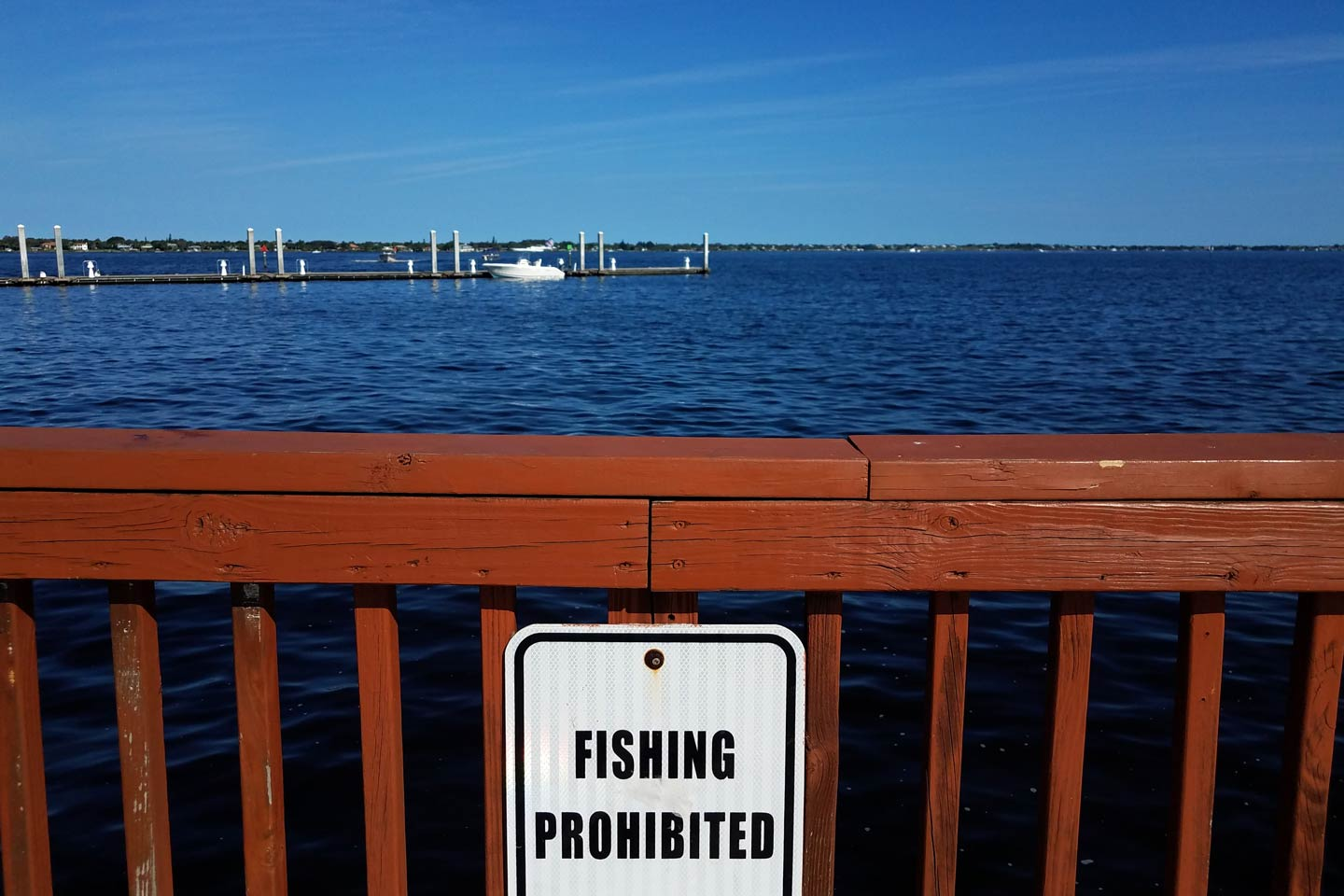 "White ""fishing prohibited"" sign on a wooden fence overlooking the water in Florida"