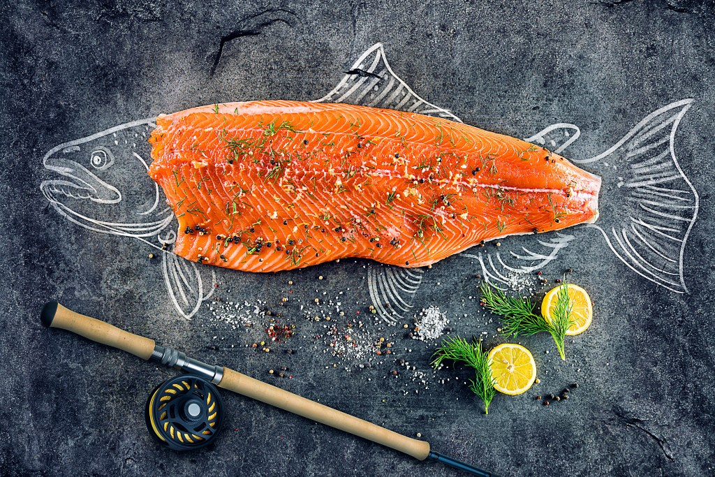 Salmon fillet with the fish drawn around it on a blackboard