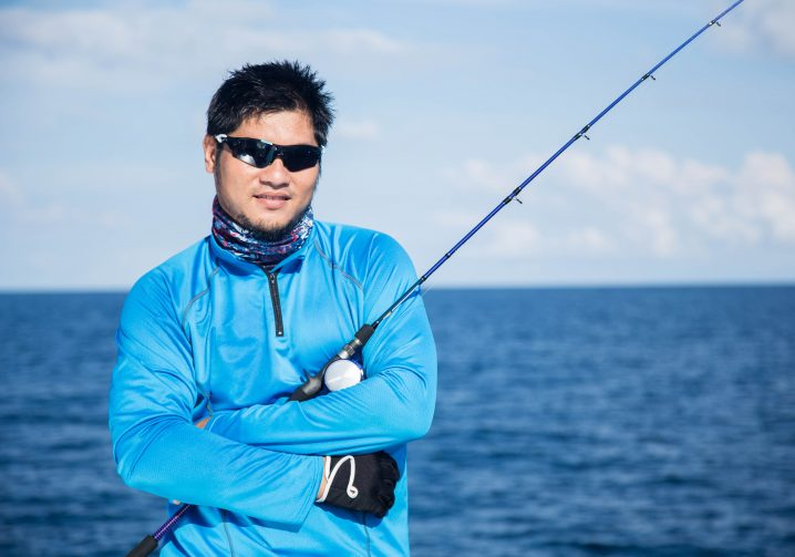 An angler in a blue white holding a fishing rod in his crossed arms with ocean and sky in the background