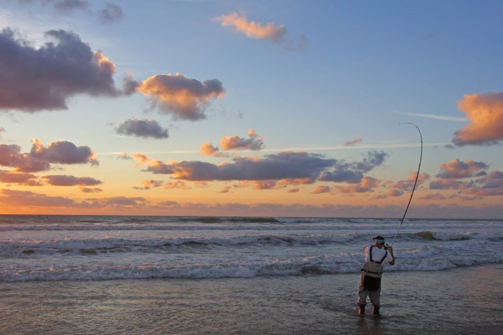 An angler casting into the surf at sunset.