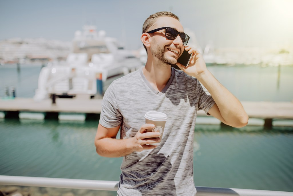 a smiling man talking over the phone with a boat and a dock in the background