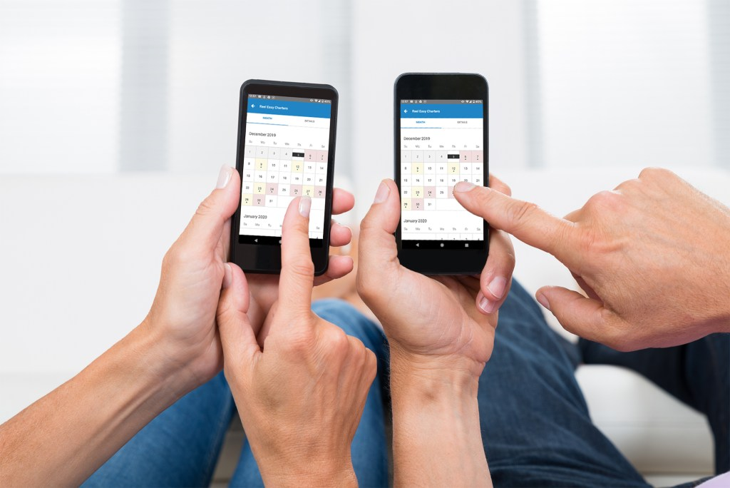two people pointing at FishingBooker's calendar app on their phones
