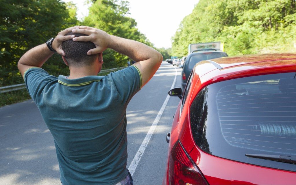 a man holding his head outside his car looking at the traffic jam ahead