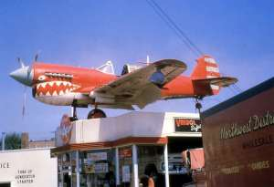 Airplane atop gas station.