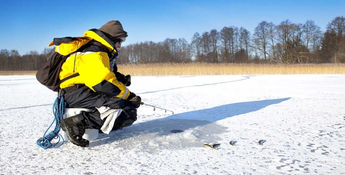 Man with ice fishing gear on the ice fishing in a whole in the ice
