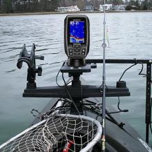 Fish finder attached to kayak on the water with fishing gear
