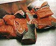 A pile of salmon cut up ready to fit into jars. Any bones will become soft and eatable with the long cooking time.