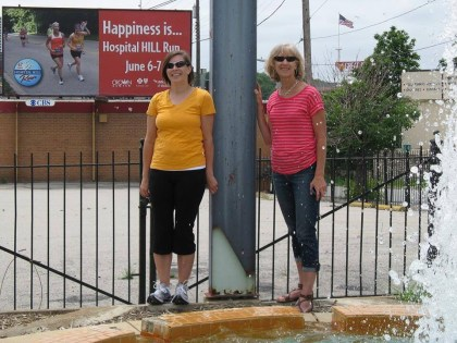 Famous run clubber Linda Pasalich with Rachel Hamby in front of the billboard that carries their photo from last year's race.