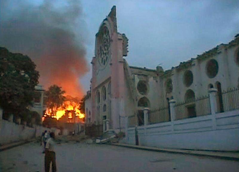 Пожар разгорелся недалеко от здания, поврежденного сильным землетрясением, в Порт-о-Пренс 12 января.