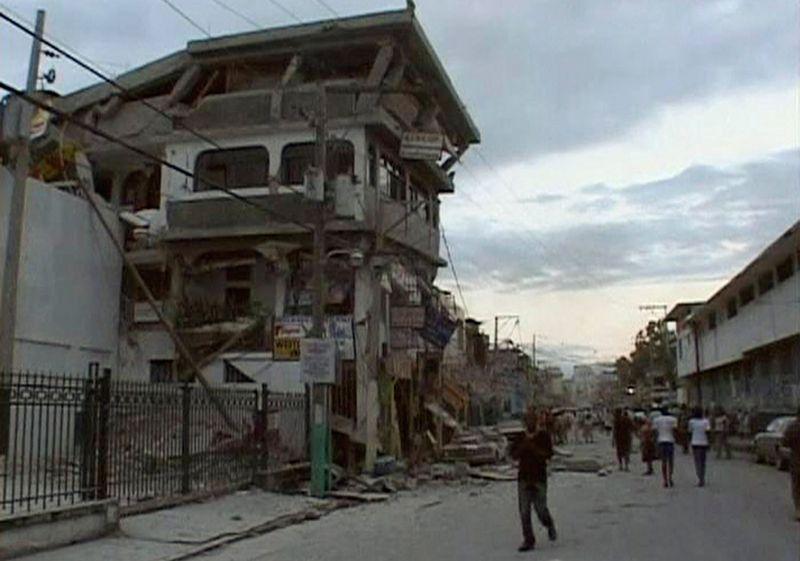 Люди идут по улице мимо разрушеных от землетрясения домов в Порт-о-Пренс 12 января.