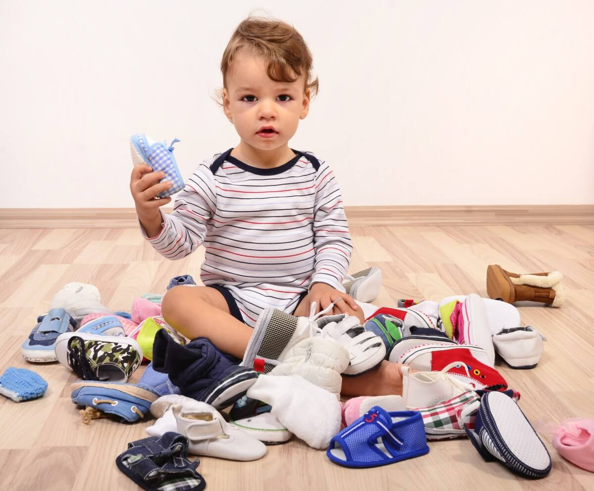 bebé rodeado de zapatos