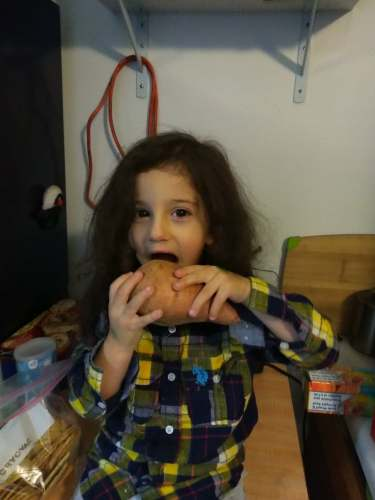 little girl eating a sweet potato