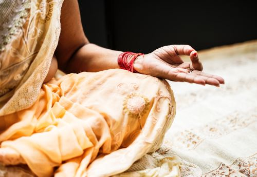 Woman sitting in meditative pose, knee, sari, and arm visible, fingers held to thumb and middle plus ring finger extended