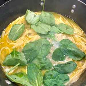 Add spinach to fettuccine and sauce