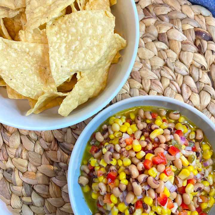 corn and black eyed pea dip in bowl with corn chips