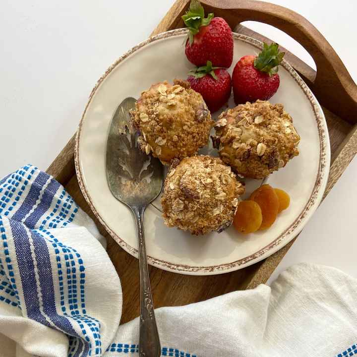 three apricot oat muffins on a plate with strawberries and dried apricots