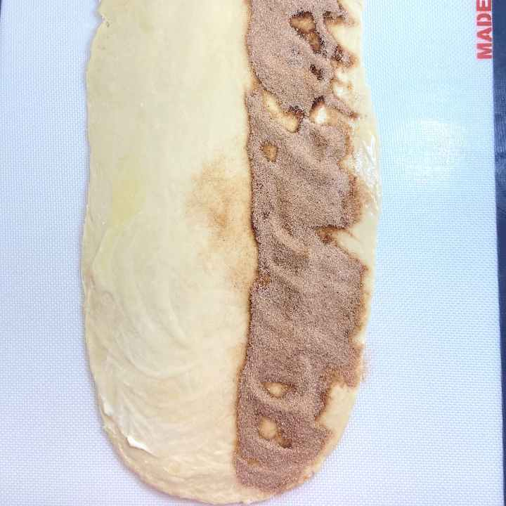 picture of rolled dough with half the length of dough sprinkled with cinnamon sugar mix.