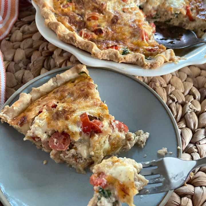 slice of ham and cheese quiche on plate