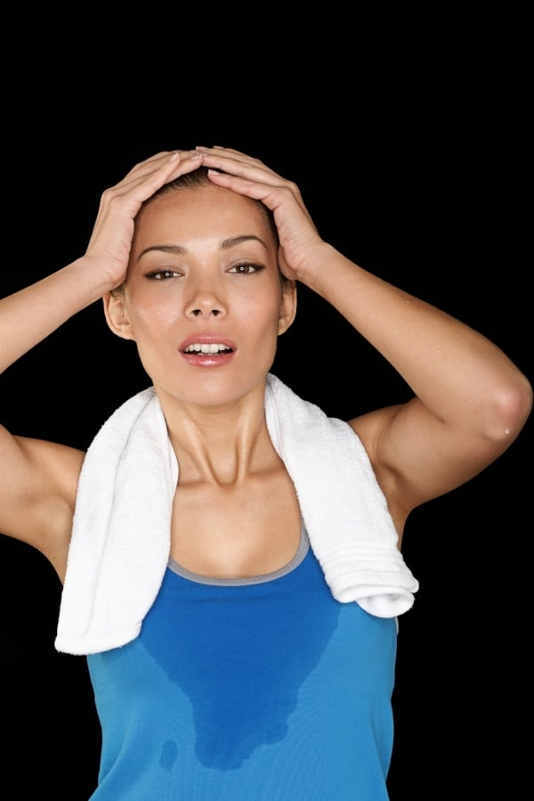 sweating woman with towel around neck