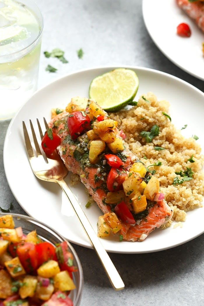grilled salmon with pineapple salsa on top next to quinoa with a lime