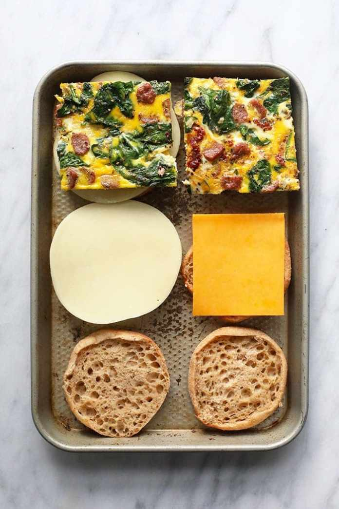 assembling make ahead freezer breakfast sandwiches on a sheet pan