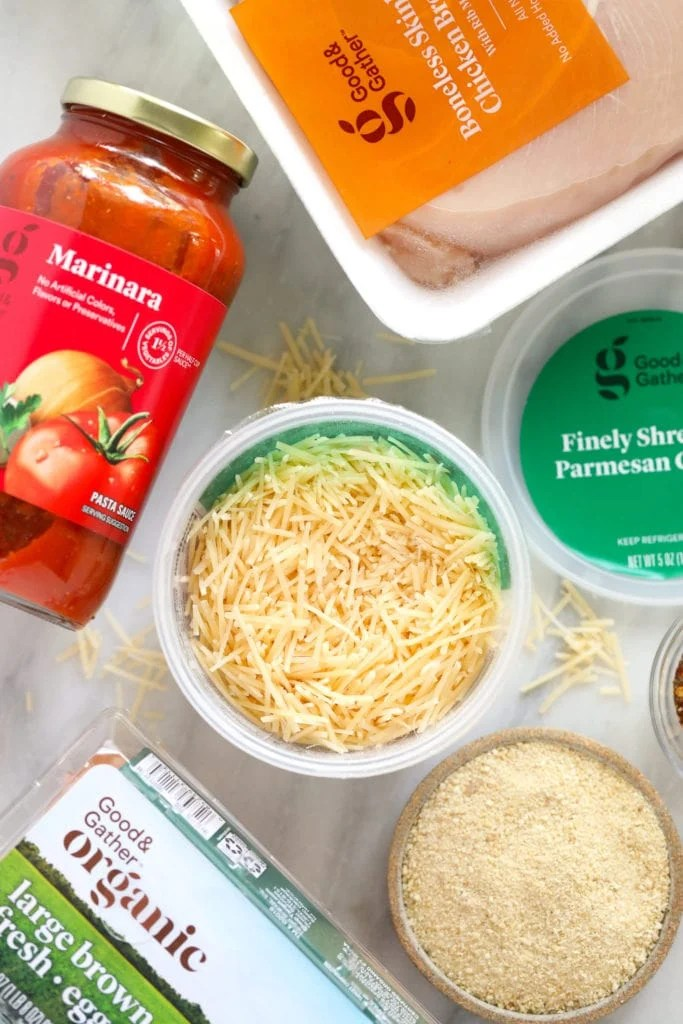 chicken parm ingredients - parmesan cheese, marinara sauce, and chicken breast