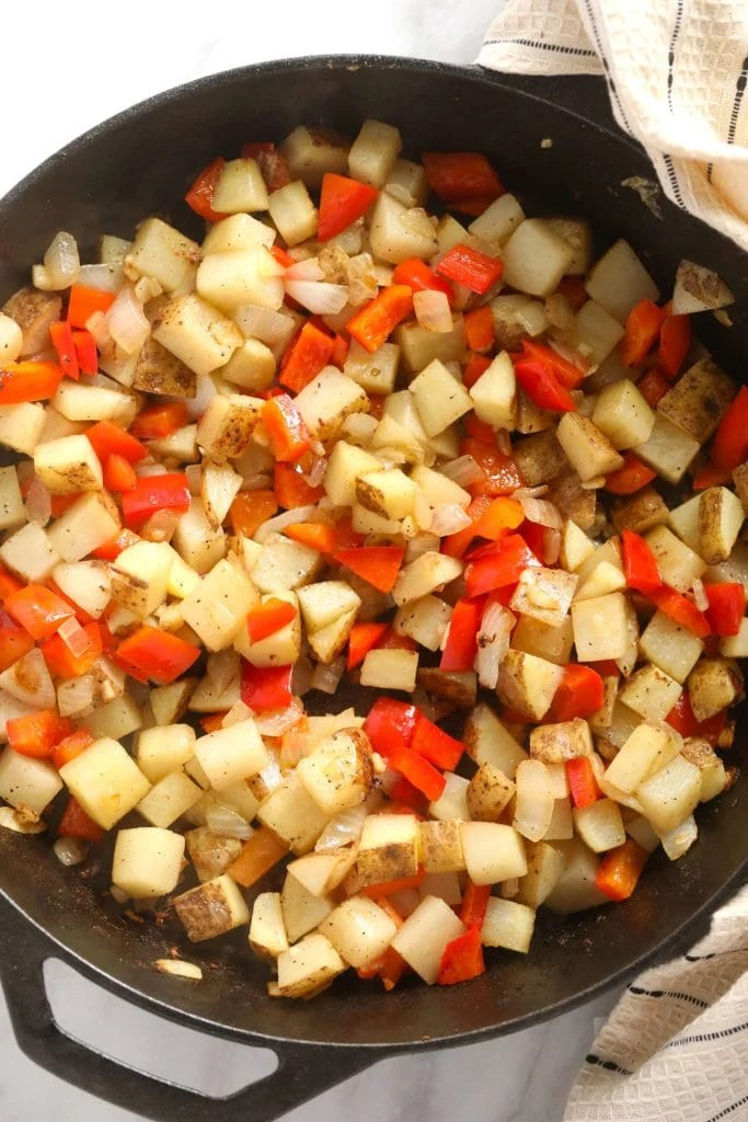 Potato cubes and red peppers in a cast iron pan