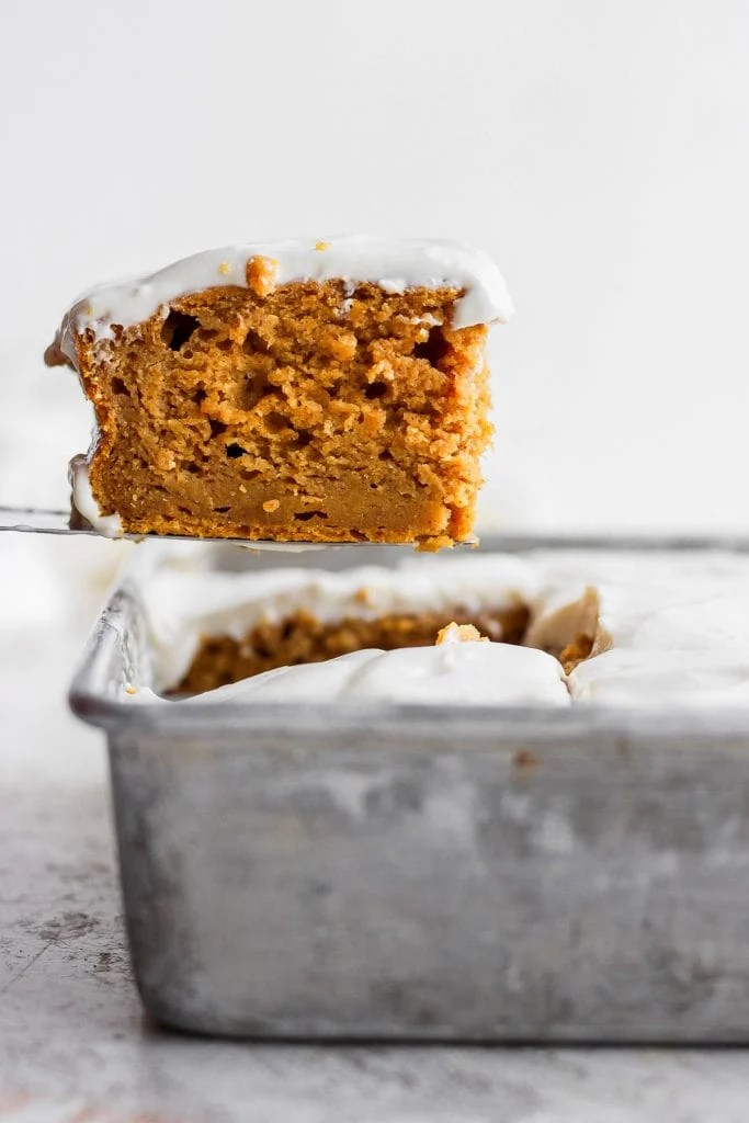 Slice of pumpkin sheet cake comes out of the pan