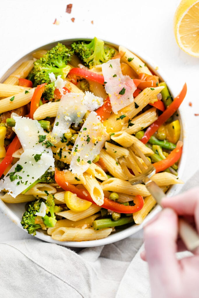 pasta primavera in a bowl topped with parmesan cheese