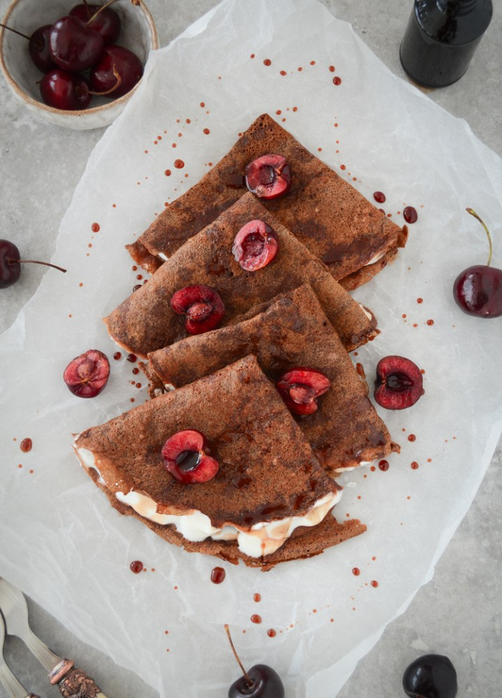 Chocolate crepes served with yoghurt and fresh cherries
