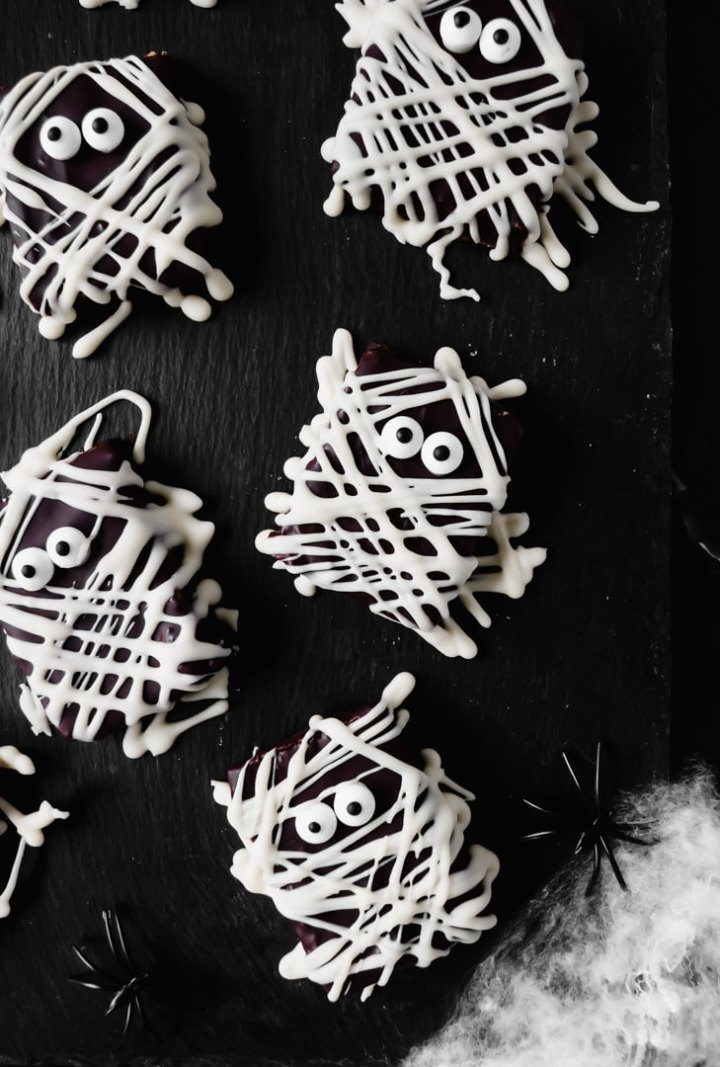 Top down view of spooky mummy chocolate bars on a black board