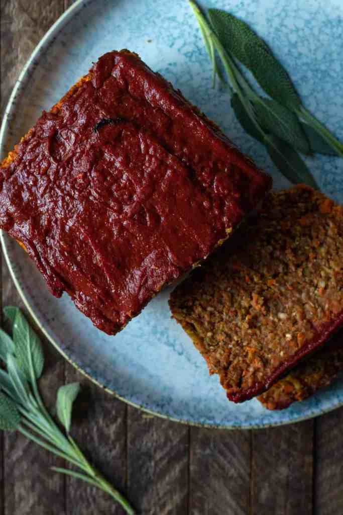 Top down view of vegan lentil and carrot loaf glazed with red sauce on a plate, sage leaves around it