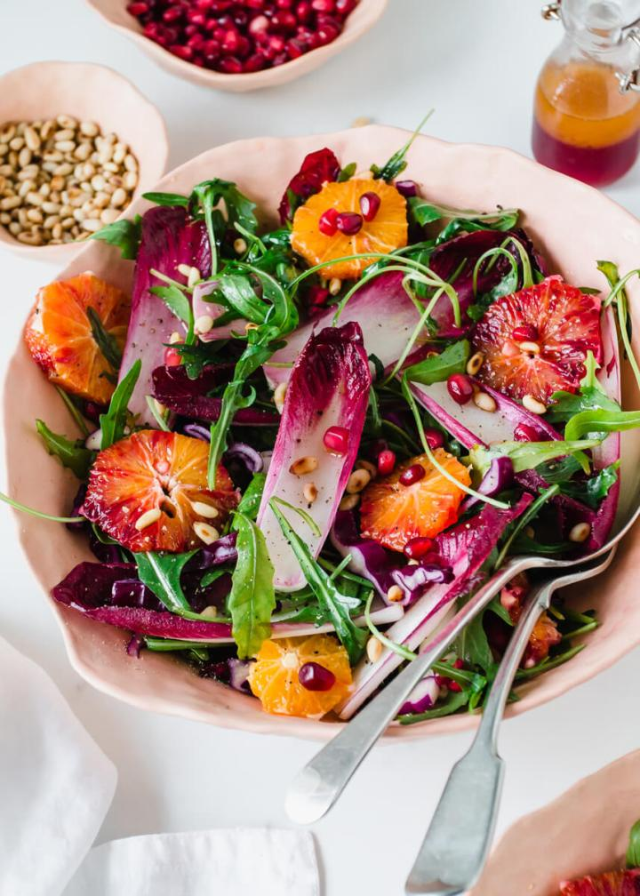 Close up view of chicory salad with rocket & blood oranges in a pink bowl