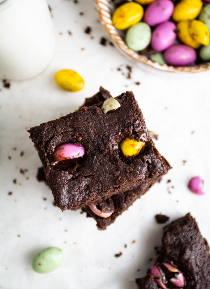 Top down view of vegan mini egg brownies, Easter chocolate eggs on the side